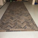 Herringbone pattern wood effect tiles inset into the 600X600 porcelain floor tiles